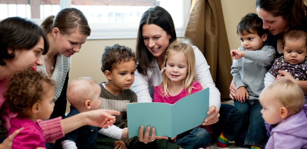 Preschool children with their mothers reading.